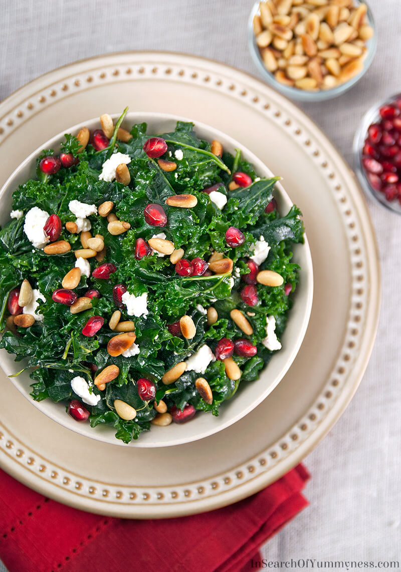 Who says healthy food can't be festive? This beautiful kale salad is made with juicy red pomegranate seeds and crunchy toasted pine nuts. Get the recipe at InSearchOfYummyness.com