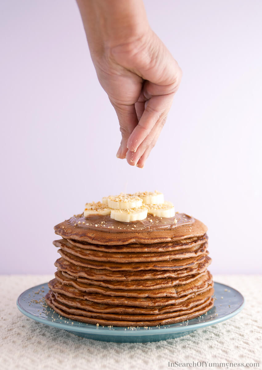 Sprinkling nuts onto Nutella Pancakes with Mascarpone Cream | InSearchOfYummyness.com