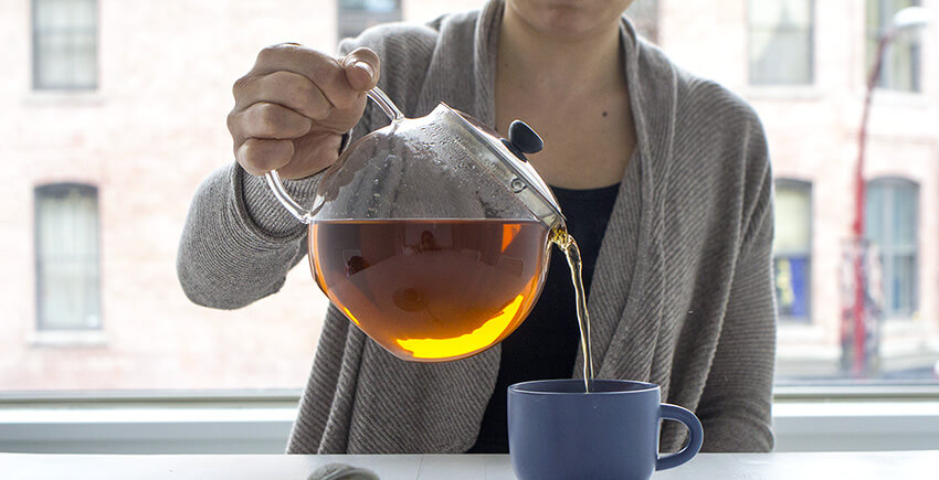 Tegan from Amoda Tea pours steeped loose leaf tea into a mug | InSearchOfYummyness.com