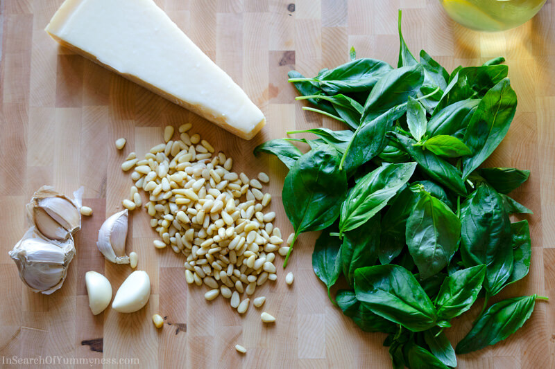 Ingredients for basil pesto including basil leaves, Parmesan cheese, pine nuts, and garlic. | InSearchOfYummyness.com